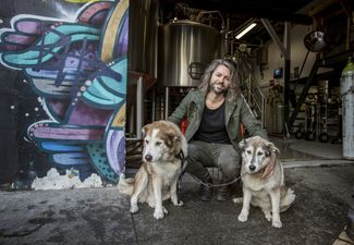 Jos crouching next to his two dogs.