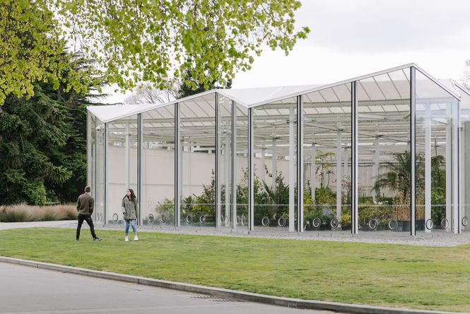 Two people standing outside the glasshouse at the Botanic Gardens.